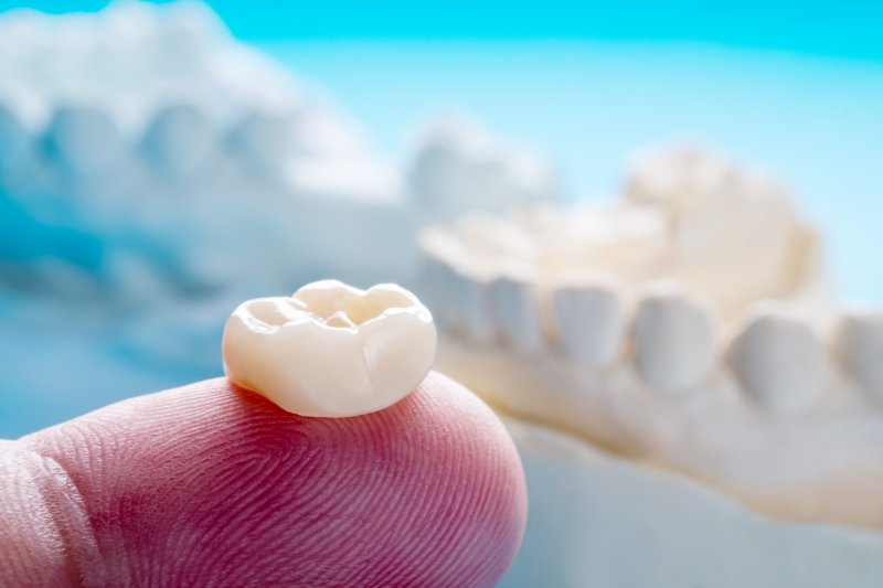 Closeup of dental crowns in Frisco, one sitting on a fingertip
