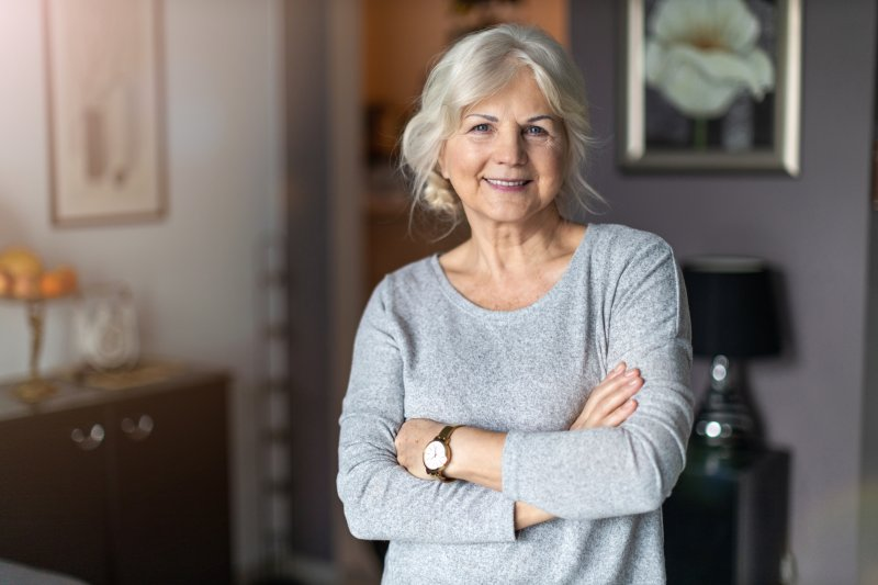 Older woman smiling with dental implants while standing with arms crossed